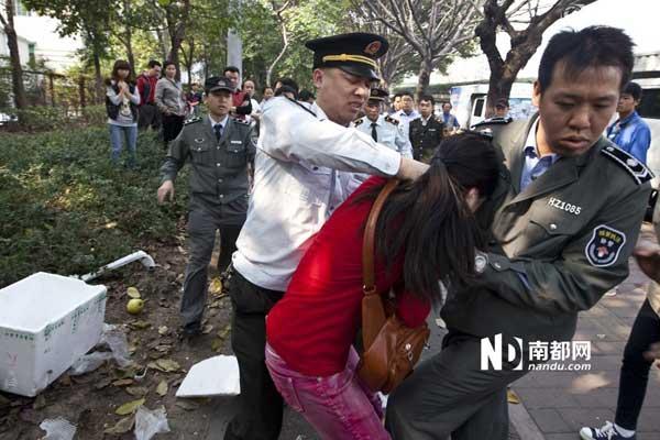 一名制服编号X080324的城管执法人员掐着女小贩脖子意图将其按倒