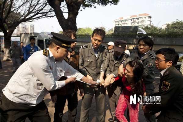 一名制服编号X080324的城管执法人员掐着女小贩脖子意图将其按倒,两人被分开后女小贩拉着该名城管的衣服。