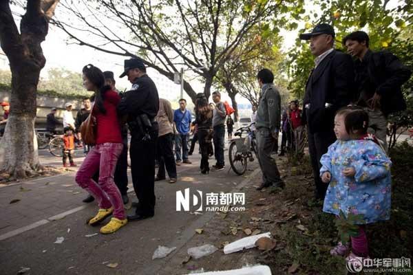 城管与女小贩发生冲突后,女小贩被警方强行带走,她的孩子在一旁放声大哭。