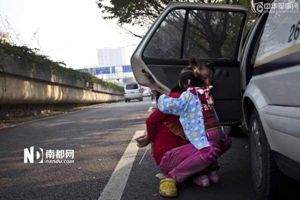 冲突发生后,女小贩的孩子惊恐地抱着她的妈妈。